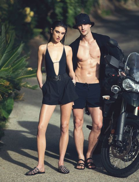 "<p><em>Polyamide and Lycra swimsuit, THAPELO PARIS, $250, visit <a href=""http://www.thapelo-paris.com/"">thapelo-paris.com</a>. Wool shorts, $675, elastane-blend belt, $825, both, VERSACE. Silver and enamel ear cuff, MARLA AARON, $125. Silver and black diamond bracelet, DAVID YURMAN, $3,200. Embellished-leather slides, ALEXANDER WANG, $595. He wears: Cotton cardigan, MICHAEL BASTIAN, $735. Nylon Lycra swim trunks, CHARLIE BY MATTHEW ZINK, $195. Cotton bucket hat, HERSCHEL SUPPLY, $35. Steel watch on rubber strap, BULGARI, price on request. Calfskin sandals, HERMÈS, $870.</em><em></em></p>"