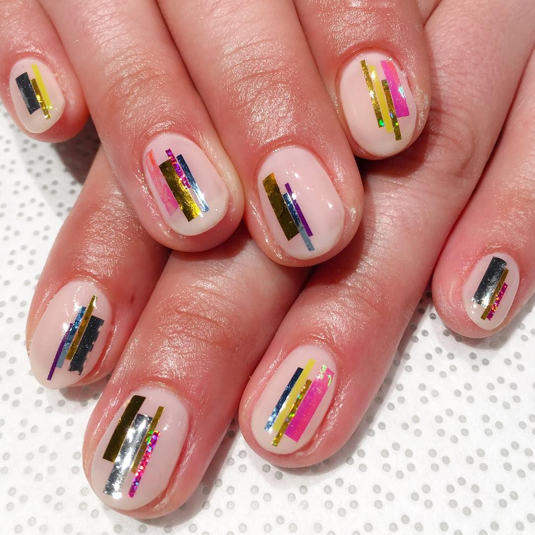 """<p>For subtle texture and sheen, try this neutral yet metallic look. Start with a nude base coat. When tacky, place strips of alternating nail tape and foil to the arrangement of your choice. Seal it with a clear topcoat. </p><p>Design by <a href=""""https://www.instagram.com/p/BGw8EZUCyR8/"""" target=""""_blank"""">@ayumutksw</a></p>"""