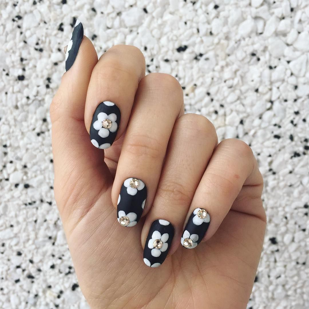 """<p>For a textured floral nail, this design mixes matte polish, regular polish and embellishments. Start with a matte base. Let dry, then paint flower petals in a glossy hue. Finish the nail with crystal accents glued to the center of each flower.  </p><p>Design by <a href=""""https://www.instagram.com/p/BC_DlewkLUO/"""" target=""""_blank"""">@jessicawashick</a></p>"""