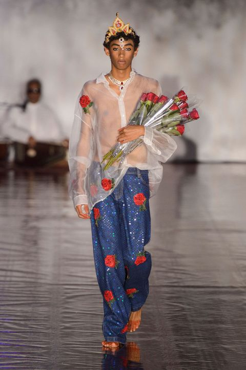 Crown, Headpiece, Fashion show, Tradition, Runway, Artificial flower, Hair accessory, Fashion design, Abdomen, Model,