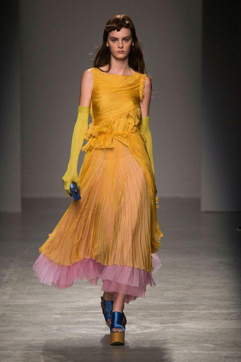 Yellow, Shoulder, Dress, Fashion show, One-piece garment, Formal wear, Style, Waist, Fashion model, Costume design,