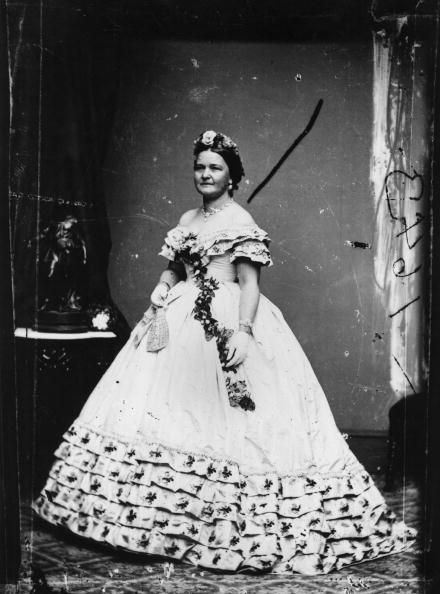 """<p>A floral headpiece and sash picks up the embroidered floral accents in the dress Mary Todd Lincoln wore for her husband's inauguration. She famously loved to shop, racking up thousands of dollars in bills for clothes and decorations for the White House (which <a href=""""http://www.mrlincolnandnewyork.org/mr-lincolns-visits/mrs-lincolns-shopping/"""" target=""""_blank"""" data-tracking-id=""""recirc-text-link"""">reportedly enraged</a> the more practical President Lincoln).&nbsp;</p>"""
