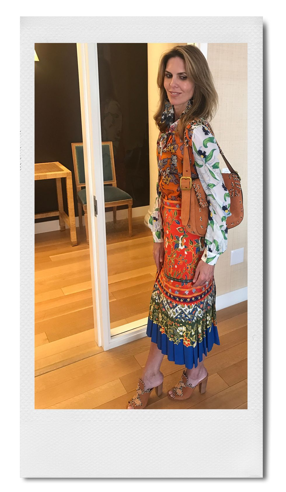 """Honor Brodie, Creative Director at Tory Burch """"When it's warmer outside I love to wear vibrant color and batik prints. This silk chiffon bow blouse adds a bit of softness to the more structured midi skirt while the embroidered suede bag and mules have a bohemian vibe that feels right for summer."""""""