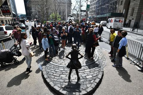 Fearless girl statue surrounded by a crowd