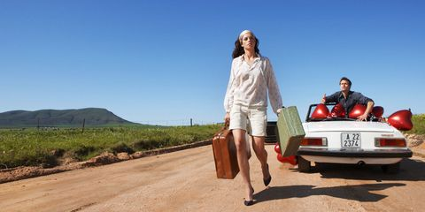 Woman walking with suitcase, man in car