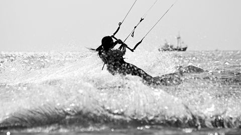 Woman Kiteboarding In Sea Against Sky