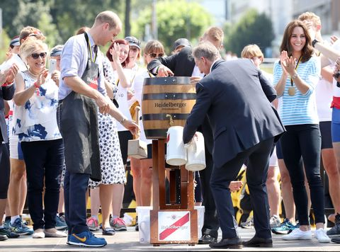 Prince William, Duke of Cambridge opens the barrel of beer after participating in a rowing race between the twinned town of Cambridge and Heidelberg and against Catherine, Duchess of Cambridge