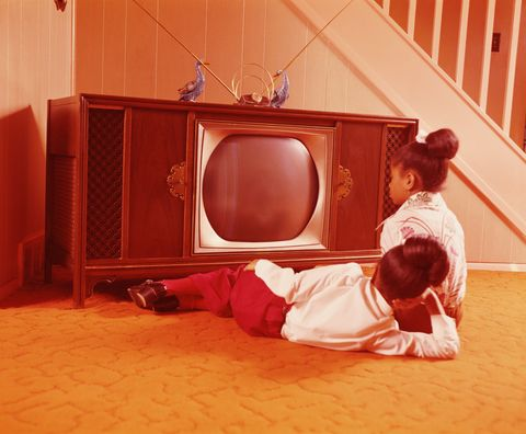 Two girls on living room floor, watching television.