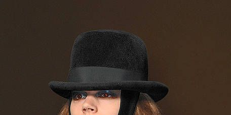Clothing, Hat, Lip, Brown, Sleeve, Human body, Collar, Coat, Outerwear, Fashion accessory,