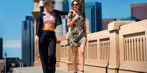 Eyewear, Outerwear, Standing, Dress, Sunglasses, Urban area, Street fashion, Waist, Tower block, Fashion accessory,