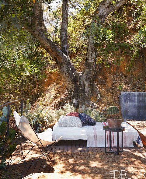 La diseñadora de moda Rozae Nichols ha mantenido un estilo rústico sofisticado en el porche de su casa midcentury de Laurel Canyon (Los Ángeles). Los cojines son de Gregory Parkinson, y la cama de día, de Van Keppel-Green. Sobre ella, una toalla turca a modo de colcha.