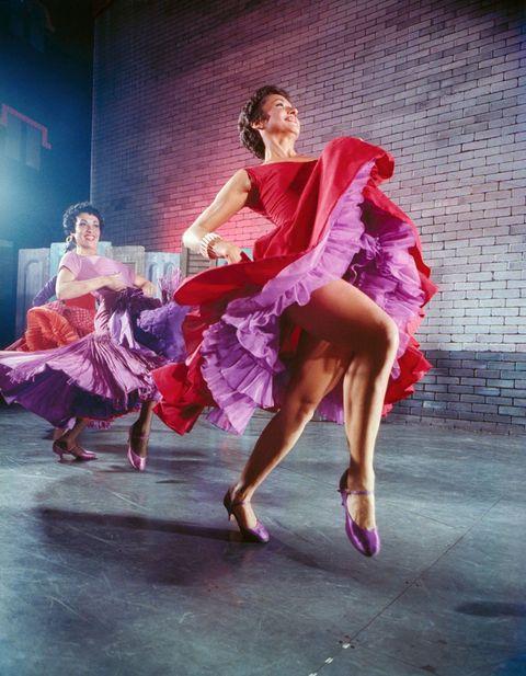 <p>Chita Rivera actuó en la producción de Broadway 'West Side Story' llevando este vibrante vestido rojo con capas de tul lila.</p><p></p>
