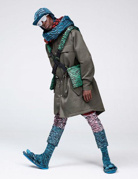 <p><strong>Oko Ebombo</strong> (músico y artista residente en París, y protagonista de la banda 19) lleva una parka con cuello extraíble con estampado, vaquero con franjas y estampado de tigre en diferentes colores y chancletas acolchadas con calcetines tabi. Además, Oko lleva una gorra con estampado de tigre con bufanda incorporada y bolso cruzado con el estampado de tigre.</p>