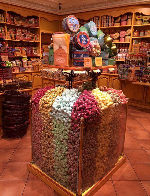"""<p>Una nota de color en medio de la ciudad, las estanterías y vitrinas parecen dibujar el arcoíris con los caramelos que hay en ellas. <a href=""""http://www.curegourmande.es/"""" target=""""_blank""""><strong>La Cure Gourmande</strong></a> es una franquicia francesa que fabrica y distribuye dulces tradicionales de elaboración natural, a día de hoy tiene 7 tiendas en nuestro país. Es casi imposible elegir entre las montañas de caramelos rellenos de fruta, bombones, galletas de sabores, <i>choupettes</i> o su famoso <i>nougat</i>, parecido al turrón. Puedes comprar a granel y meter el producto en las preciosas latas de estilo <i>vintage</i> que venden, o surtidos de variados, que por su <i>packaging</i> son ideales para regalar. Uno de sus grandes éxitos son las aceitunas de chocolate, todo un trampantojo.</p><p>Postas, 18 (Madrid).</p><p>Ferrán, 14 (Barcelona)</p><p>Jaume II, 34 (Mallorca).</p><p>Alfonso I, 43 (Zaragoza).</p><p>Rúa Mayor, 35 (Salamanca).</p><p>Comercio, 23 (Toledo).</p><p>Sierpes, 2-4 (Sevilla).</p>"""