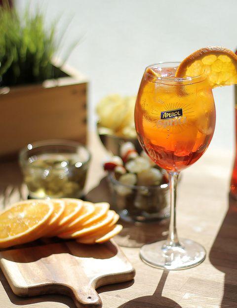 <p>El <strong>Aperol Spritz</strong> es una leyenda italiana y uno de los cócteles más consumidos en este país. Si quieres elaborarlo al estilo veneciano solo tienes que seguir esta sencilla receta.</p><p><strong>Ingredientes:</strong></p><p>- 3 partes de prosecco o cava.</p><p>- 2 partes de Aperol.</p><p>- 1 parte de soda.</p><p>- Naranja.</p><p>- Hielo.</p><p><strong>Elaboración:</strong></p><p>Coge una copa de vino y añádele mucho hielo. Vierte el prosescco, el Aperol y la soda por ese orden. Remueve para que se mezclen bien los ingredientes y decora con una rodaja de naranja.</p>