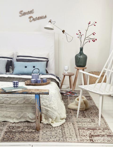 <p>Ya lo anuncian las letras sobre la cama, de Woonexpress XL: tener dulces sueños en este dormitorio es muy fácil. Lo hacen posible los cálidos complementos: colcha gris, mod. <i>Tallört</i>, de Ikea; cojín azul de fieltro, de Shed 5 Design; taburetes, de Nijhof, con jarrón, de Woonexpress XL; lámpara <i>Ranarp</i>, de Ikea; banco de madera, de The Cabinet, y silla, de Shed 5.</p>