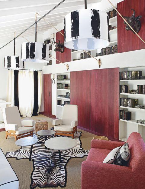 <p>La madera de esta tonalidad se convierte en un potente elemento decorativo, sobre todo en el alzado de la librería que preside el salón. Combina a la perfección con la clásica alfombra de piel de cebra, adquirida por los propietarios de la casa.</p>