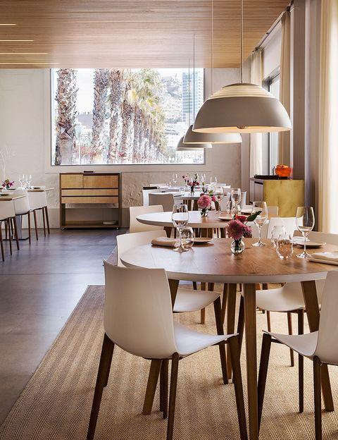 """<p>Joël Robuchon, el cocinero con más condecoraciones de todos los tiempos –suma hasta 28 estrellas–, tiene un pequeño placer que se hace posible en esta ciudad portuaria: sentarse a la barra de azulejos de Nou Manolín, un local clásico donde las sillas de enea conviven con paredes asaeteadas de fotos, incluidas imágenes de Penélope Cruz y Manolete (<a href=""""http://noumanolin.com"""" target=""""_blank"""">noumanolin.com</a>). El midas francés de la restauración afirma que esta es «la mejor barra del mundo». Damos fe de ello iniciándonos con sus gambas blancas, casi del tamaño de carabineros, preciadas por vivir en las limpias profundidades y por ese puntito de sal que tiene aquí el mar. Lo bordeamos por la famosa ola de adoquines del paseo marítimo. Allí somos de los primeros en estrenar la única estrella Michelin de la capital, Monastrell (en la imagen), que rinde homenaje con su nombre a la uva icónica de esta región (<a href=""""http://monastrell.com"""" target=""""_blank"""">monastrell.com</a>). Se trata de un espacio fresco, sin manteles, lleno de peonías y que apuesta por la cocina sostenible. Les hacemos una reverencia a los arroces integrales con picadillo de jamón ibérico creados por su dueña, la chef María José San Román. «Aquí resumo lo que se da en la provincia de forma sabrosa pero sana; ese es el camino hacia una comida sensata», asegura esta maga conocida como la Reina del Azafrán.</p><p>Nuestra segunda cita foodie es en El Portal (<a href=""""http://elportaltaberna.com"""" target=""""_blank"""">elportaltaberna.com</a>): buen producto servido con desenfado, también para celiacos y veganos. Mitad gastrobar, mitad verbena, es uno de esos lugares de los que no apetece irse; empiezas con una tapa de arenque con guacamole y helado de fruta de la pasión a mediodía y acabas con un gin tonic amenizado por un DJ a las siete de la tarde. Aquí catamos Triga, un caldo alicantino que nos descubre su chef, Sergio Sierra, mientras nos muestra, a puerta cerrada, su nueva aventura: Teatro Bistrot (<a"""