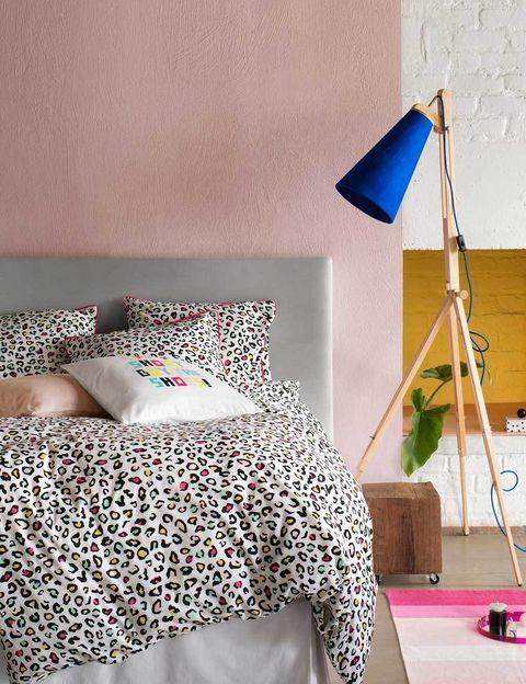 <p>Literalmente, porque en este dormitorio el descanso se hace muy goloso, gracias a la pared en rosa palo y el cabecero gris nórdico. El punto de color lo pone la lámpara, con pantalla en azul klein, y la ropa de cama con print felino, de H&amp;M Home.</p>