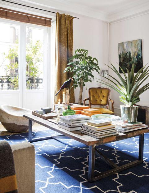 <p>La pintura blanca, de Farrow &amp&#x3B; Ball y todas las plantas, de Fransen et Lafite, potencian la luminosidad. Las cortinas de terciopelo son de Gastón y Daniela&#x3B; el kilim azul, de Kilombo Rugs, y el puf de madera, de una artista holandesa. La mesa de centro es de Timothy Oulton.</p>