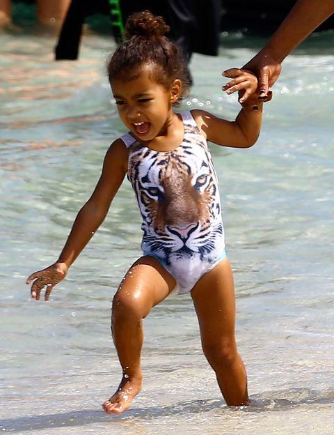 <p>Hasta en sus vacaciones North West es toda una 'it girl' en miniatura. La pequeña luce un look muy 'salvaje' con este bañador con un tigre estampado.&nbsp;</p>