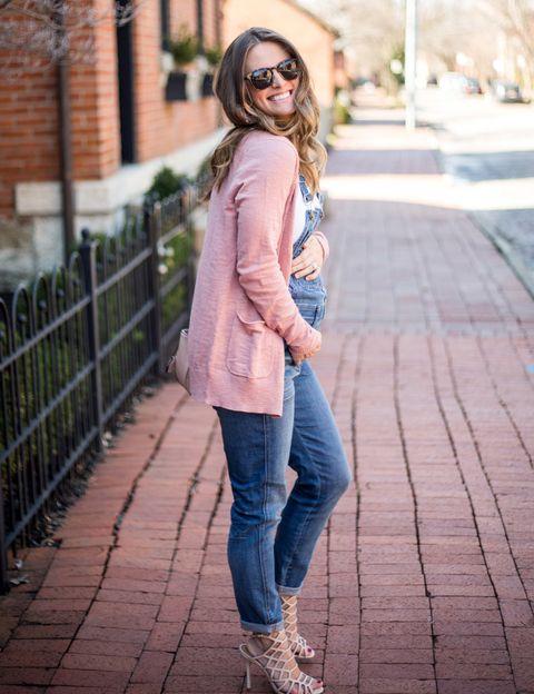 <p>Una manera acual de llevar el embarazo, con un peto denim y chaqueta de punto rosa.</p>