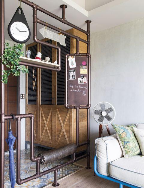 <p>Con baldosas, de Roman Granit, el recibidor se delimita visualmente con una estructura de tubos de hierro que evita tener una visión directa de la ventana al entrar en casa, algo prohibido por el feng shui.&nbsp;</p><p>&nbsp;</p>