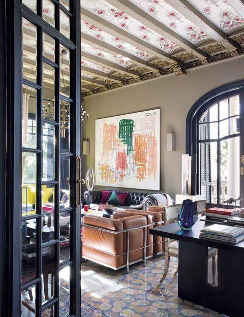 <p>Preludian un salón extra luminoso. En la mesa negra de Porro destaca un jarrón azul de Bohemia tallado a mano de Moser. Unos sofás chester de cuero y butacas&nbsp;<i>LC2</i>, de Le Corbusier que edita Cassina, decoran el estar; al lado, escultura en peana de Adolfo Estrada. Papiol firma el modelo que &nbsp;viste el suelo de la entrada.&nbsp;</p>