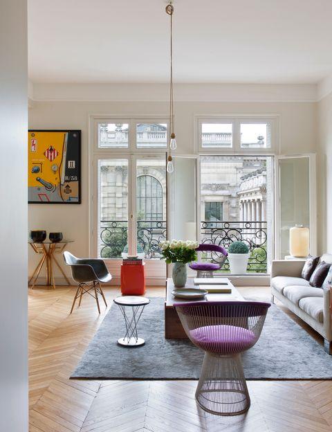 <p>Pero no a los de la propia casa, sino a los del Palais Galliera. En morado, el sillón <i>Side Chair</i>, de Warren Platner para Knoll; y en negro, la <i>Eames Plastic Chair</i>, editada por Vitra. La mesa auxiliar naranja <i>Oko</i> es de Christophe Delcourt. En la pared, cuadro de Peter Klasen.&nbsp;</p><p>&nbsp;</p>