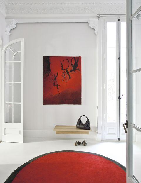 <p>En la entrada, con suelo de mortero de cal, de Kourasanit, una clara apuesta por el color con afombra <i>Aros Round 1,</i> de Nanimarquina, y cuadro <i>ZWEI</i>, de Perico Pastor. Bolso de Bottega Veneta y zapatos de Vialis.</p>