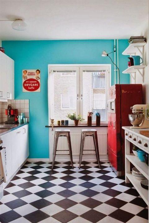 <p>Todo un clásico de las cocinas vintage, se alegre con la pared pintada de azul turquesa y el frigorífico rojo. Los taburetes metálicos son el mod. <i>Tolix.</i></p>
