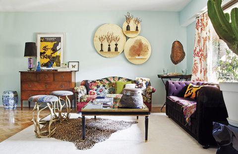 <p>Flora y fauna marina decoran con sus alegres estampados y divertidas formas el salón. Los sofás son un diseño de María Zurita. La mesa de centro y los asientos con patas de rama son de Anmoder. La lámpara sobre la cómoda de madera y, en la mesa auxiliar, el caparazón de tortuga, de El Ocho. La alfombra de leopardo es de Zara Home. En la pared, corales de Teresa de la Pisa.</p>