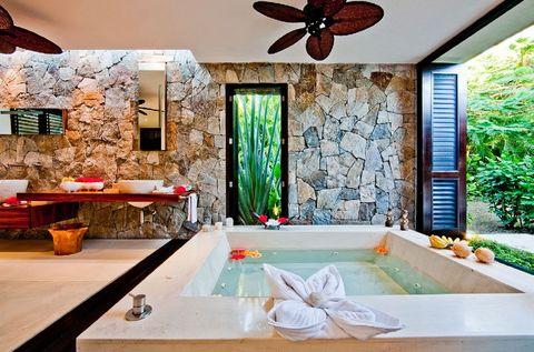 <p>La exuberante vegetación de Nayarit (México) se cuela en este baño, perteneciente a una villa llamada Casa Kalika. La bañera de mármol con hidromasaje ofrece unas vistas privilegiadas.</p>