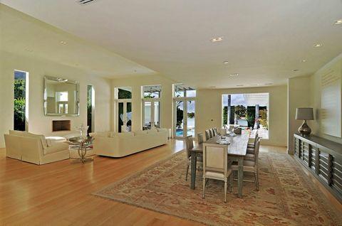 <p>Salón y comedor se integran en el mismo espacio, que también dispone de chimenea. Esto le daría un toque muy confortable... si no estuviera en Miami. </p>