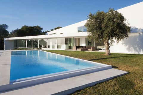 <p>Una piscina de agua salada de 17x5 m, realizada con hormigón, invita al relax en el jardín. Al fondo, el porche, con sofás y mesa de Royal Botania. En el interior puede verse la cocina y uno de los dormitorios.</p>