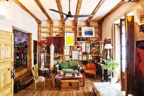 <p>Con una estupenda biblioteca de madera, obra del hermano de Mabel, autor también de los cuadros en tonos rojos y del fresco de la habitación anexa. El resto de los cuadros son de Mabel y el baúl de madera y las butacas tapizadas son recicladas.</p>