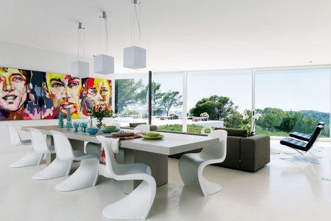 <p>Las míticas sillas <i>Panton,</i> de Vitra, acompañan la mesa del comedor, un diseño de gran formato de Patrick M. Encima, jarrones de cristal, vajilla y copas, en Sluiz, al igual que el plaid de Missoni. Un trío de lámparas de techo <i>Jeti S,</i> de Delta Light, ilumina el ambiente. El plus de estilo lo ponen el cuadro <i>Triptyque,</i> de Françoise Nielly, y las butacas modelo <i>Barcelona,</i> de Mies van der Rohe, editadas por Knoll.</p>