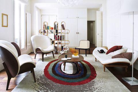 <p>Los muebles de líneas curvas marcan este diáfano espacio. La estantería <i>Isis,</i> diseñada por Jean-Marc Gady, al igual que la silla de rejilla<i> Yume,</i> fabricada por Perrouin, delimita visualmente la entrada de la zona de estar. Sobre el sofá de cuero blanco, unos artesanales cojines.</p>