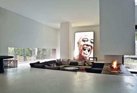 <p>El salón familiar está diseñado con el estar excavado en el suelo y rematado por una chimenea. Al fondo, obra de Fathi Hassan, procedente de la colección <i>M'Afrique</i> de Moroso. Pufs mod. <i>Kub,</i> de Nendo, en varias versiones.</p>