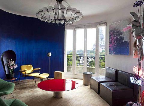<p>Pierre Paulin firma los asientos verdes del salón y el que lleva reposapiés amarillo. La lámpara del techo y la de pie son diseños de los '50, de Gino Sarfatti; la pieza cuadrada a modo de caja es de Constantin Krzic, y la mesa de centro roja, una pieza de Martin Szekely.</p>