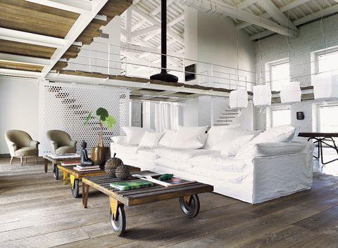 <p>Una armónica composición formada por piezas de gran tamaño llena el amplio espacio de la casa. Carritos de tren hacen de mesas de centro; el sofá <i>oversize</i> con fundas blancas es un diseño de Paola Navone para Linteloo, y detrás, una gran mesa multiuso.</p>