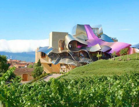 """<p> El espectacular diseño de su edificio, de arquitectura vanguardista, está firmado por Frank O. Gehry. El canadiense quiso plasmar los colores representativos de los vinos Marqués del Riscal -rosa, oro y plata-, y aportar un toque futurista con un revestimiento de titanio. No es de extrañar que haya sido escenario de numerosas producciones de moda.<br /><a href=""""http://www.hotel-marquesderiscal.com"""" title=""""Hotel Marqués de Riscal Elciego"""" target=""""_blank"""">www.hotel-marquesderiscal.com</a></p><p></p>"""