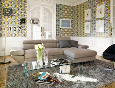 <p>¿Y si no pones todo el papel pintado de arriba abajo de la pared? Combinar papel y zócalo resulta muy elegante, sobre todo si es un zócalo alto, como el del salón de la imagen, renovado gracias al <i>print</i> geométrico</p>