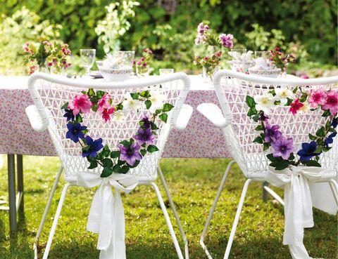 <p>A veces, los detalles de la decoración no están en las mesas, sino en otras partes del entorno. Fíjate en la imagen&#x3B; se ha aprovechado la reja del respaldo de la silla para adornarla con unas coronitas en forma de corazón y un lacito blanco.</p>