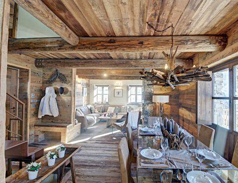 <p>Salón y comedor están unidos y, como en el resto de la casa, destacan los materiales naturales como la madera y la piedra.</p>