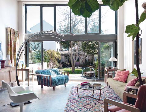 <p>Una estancia que define el espíritu de la propietaria, con alfombra bereber marroquí procedente de la casa de los padres de Corine; mesa baja <i>Stella</i>, de Noé Duchaufour Lawrance; butaca <i>InOut,</i> de Paola Navone, con <i>plaid</i> azul, de Bon'homme; y lámpara estilo arco, diseño italiano de los 70.</p>