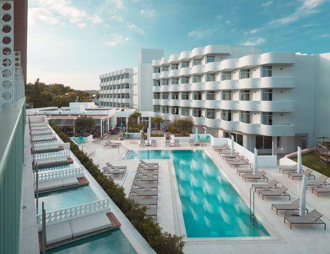 <p>La piscina, diseñada con líneas sutiles y elegantes, preside el espacio común situado entre los dos edificios. Las tumbonas son el mod. <i>Landscape,</i> de Kettal, y el suelo, de maxilosetas, de Floor Gres.</p>