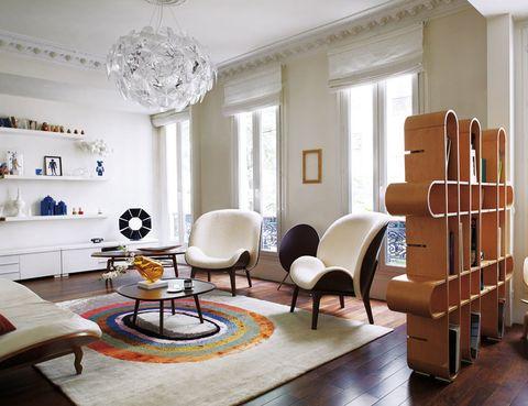 <p>La lámpara <i>Hope,</i> de Luceplan, ilumina el estar. Este ambiente se ha decorado con los sillones y la <i>coffee table</i> de la colección <i>Hug,</i> ideada por Jean-Marc Gady para Perrouin. La alfombra <i>Race</i> es otro diseño de Gady para Hadjer Gallery y la consola es de Poliform. Al fondo, unos simples estantes, perfectos para resaltar objetos fetiche como el despertador japonés de los 70, el teléfono <i>Symbio</i> de Thompson o la lámpara <i>Paradise,</i> de Jean-Marc Gady.</p>