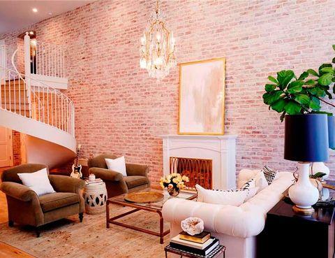 <p>La imponente pared de ladrillo visto de 6 m de altura sirve de marco a una combinación de piezas clásicas y vintage. Una elegante escalera de caracol en forja blanca da acceso al piso superior.</p>