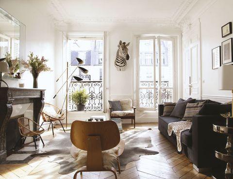 <p>Así es el estilo del salón Lámpara italiana vintage, de Galerie Avril; butacas de ratán vintage con cojín <i>Tropic Adeline Affre,</i> en Smallable. En el sofá, manta con print de leopardo, de Lindell &amp; co. En primer término, butaca <i>LCW</i> de los Eames; A la dcha., pedestal de cerámica y lámpara de mármol, de&nbsp; India Mahdavi. Alfombra de piel de vaca, en Smallable. En la chimenea, lámpara de Foscarini.</p>